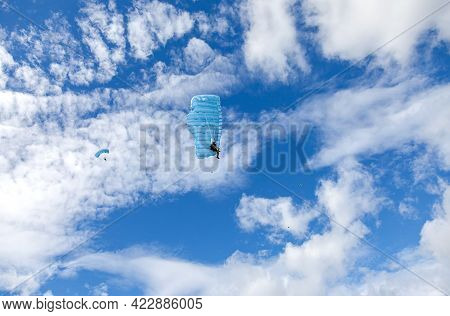 Parachute Jumpers On A Blue Wing Parachute On A Blue Sky Background