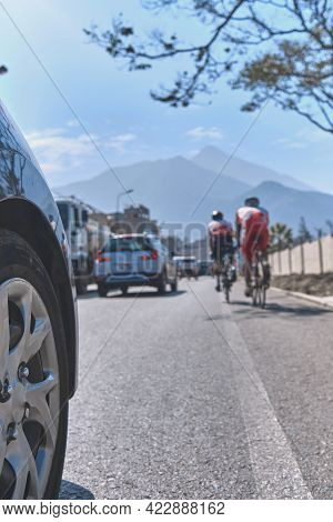 Professional Cyclist Training On The Road With Safety Escort Car. Cyclist Followed By Team Car. Sele