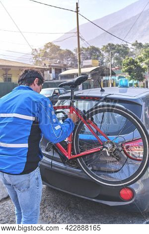 Man Cyclist Guard Loading His Bicycle On A Rack Of His Crossover Car, Safety Escort Car. Selective F