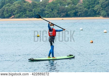 A Young Woman Paddle Surfing In The Sea In Urdaibai, A Bizkaia Biosphere Reserve Next To Mundaka. Ba