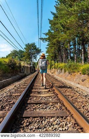 A Young Woman Walking Along The Train Tracks Of Urdaibai, A Bizkaia Biosphere Reserve Next To Mundak