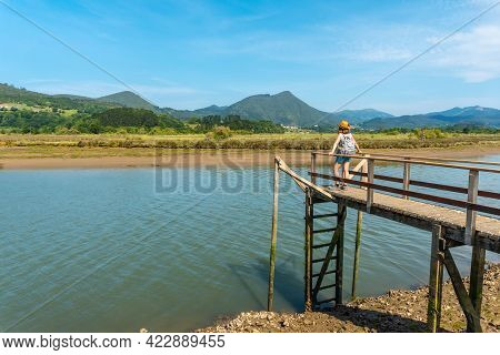 A Young Woman On The Wooden Piers Of The Urdaibai Marshes, A Bizkaia Biosphere Reserve Next To Munda