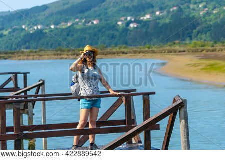 A Young Woman Looking At The Birds From The Wooden Piers Of The Urdaibai Marshes, A Biosphere Reserv
