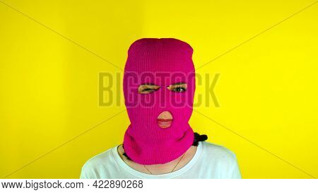 Close Up Of Unrecognizable Woman In Pink Balaclava Winks On Yellow Background. Unknown Female In Mas