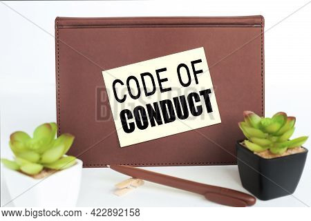 Code Of Conduct. Inscription On A Sticker On A Notebook On A White Background. Notebook Near The Flo