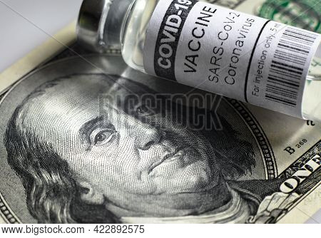 Vaccine Vial From Covid-19 And Dollar Bill, Franklin Portrait On Us Money Banknote And Coronavirus D