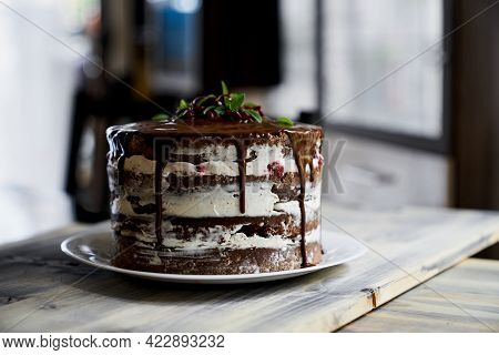 Chocolate Brownie Cake Topped With Dark Chocolate Ganache On A Wooden Table