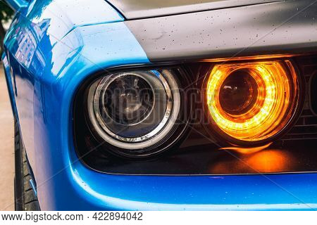The Front The Front Double Headlight Of A Sports Blue Car. Orange Headlight.