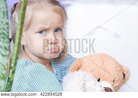 Offended Girl Makes A Face With An Offended Lip At Home. Girl Hugs A Stuffed Bear Toy