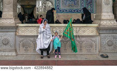 Shrine Of Fatima Masumeh, Qom, Iran - May 2019: Iranian Women And Her Daughter Holding An Islamic Ba