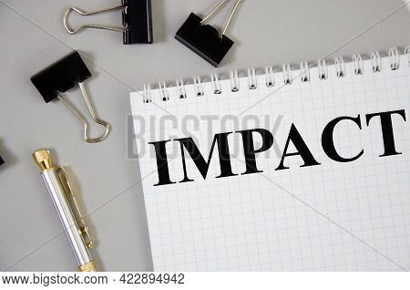 Impact Word Written On Gray Background With Pencils And Paper Clips. Text