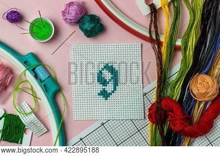 Green Number 9 Cross-stitch Embroidered Surrounded By Accessories For Embroidery: Threads Of Moulin