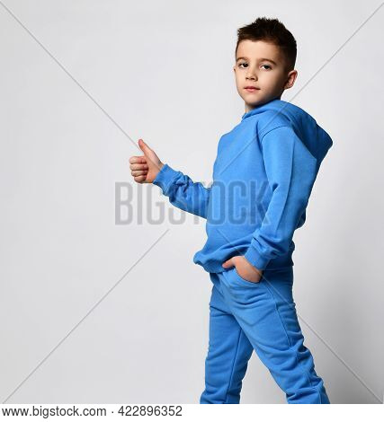 Child Likes Clothes. Schoolboy In A Blue Tracksuit Stands Sideways And Shows A Cool Sign By Raising