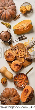 Flat-lay Of Female Hands Cutting Pumpkin On Wooden Board