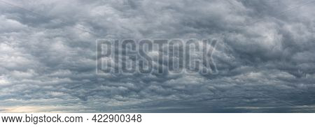 Low Gray Stratocumulus Clouds Covered The Whole Sky. Dark Overcast Sky Panorama. Wide Image Of Sceni