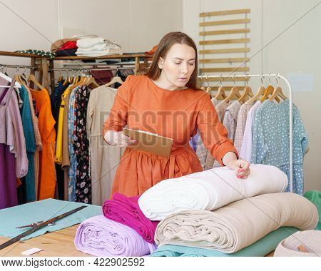 Fashion Business. Busy Young Woman Fashion Designer Dressmaker Checking Rolls Of Fabric In Workshop