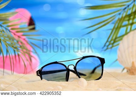 Summer Relaxing Beach Concept. Sunglasses On The Sand On The Sandy Seashore. Palm Leaves, Seashells