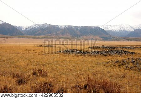 Remains Of Ancient Burials In The Autumn Steppe Surrounded By Snow-capped Mountain Peaks.