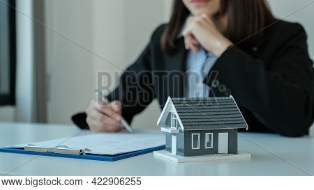 Home Model. Hand Signing On Contract After The Real Estate Agent Explains The Business Contract, Ren