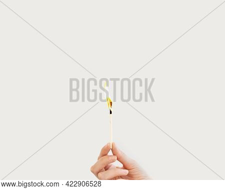 Woman Hand Holds Lit Match On White Background. Wooden Matchstick Is Burning. Fire Hazard Concept.