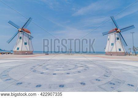 Seochon, South Korea; June 2, 2021: Two Windmills At Chunjangdae Beach On Sunny Day With Hazy Blue S