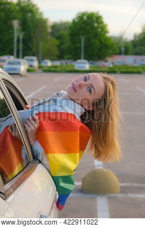 Young Blonde Millennial Woman With Lgbtq Flag Looking From Car Window. Rainbow Lgbt Flag. Peace And
