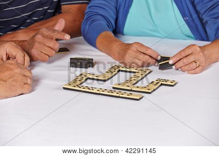 Hands of three old seniors playing a domino game