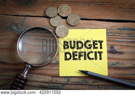 Budget Deficit. Euro Cash And Magnifying Glass On A Wooden Background