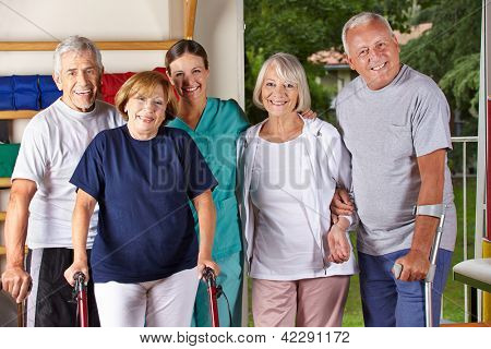 Group of happy senior people in gym with physiotherapist