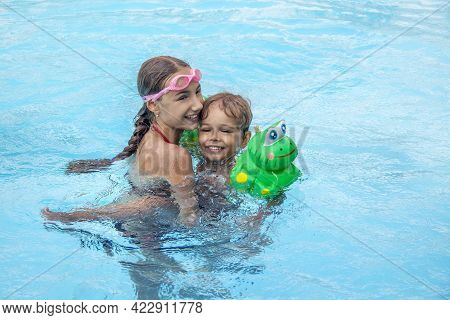 Happy Brother And Sister Swim In The Pool. Smiling Girl And Boy Are Playing In The Pool. The Concept