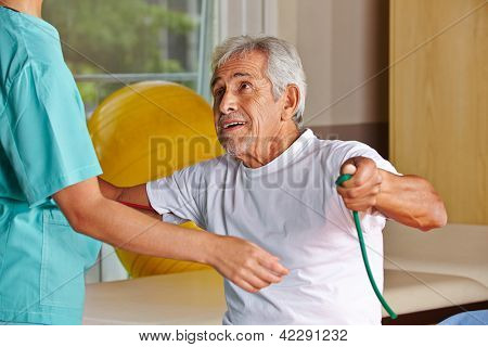 Senior man at rehab with nurse pulling on a string