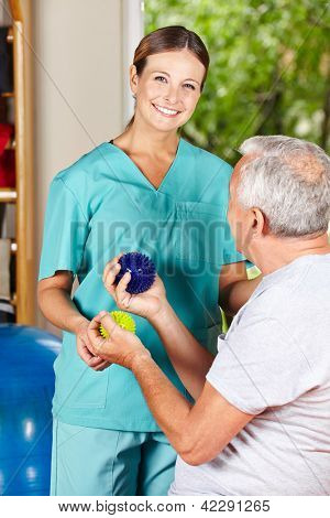 Physiotherapist showing senior man an exercise with a spikey ball