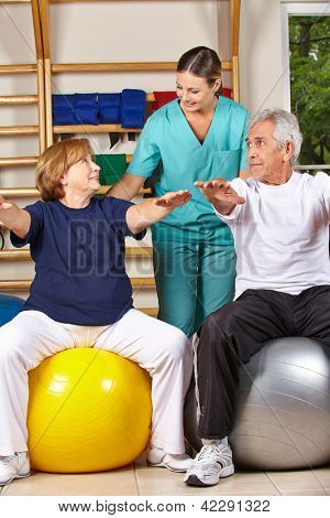 Two senior people doing back fitness training with physiotherapist