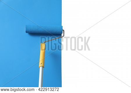 Applying Light Blue Paint With Roller Brush On White Wall