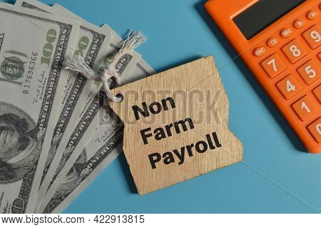 Top View Of Calculator, Money Banknotes And Wooden Board Written With Non Farm Payroll.
