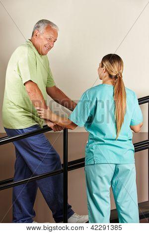 Senior man on treadmill with physiotherapist holding railing