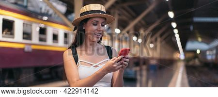 Young Brunette Woman Traveler Laughs While Playing A Mobile Phone In Train Station Platform. 20s His