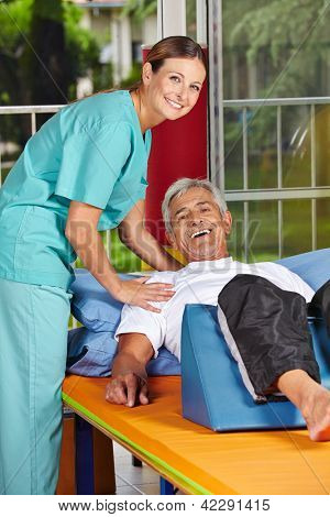 Handicapped senior man at rehab with physiotherapist