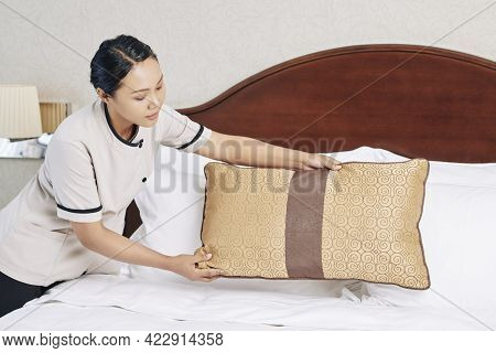 Hotel Maid Decorating Bed With Throw Pillows When Preparing Room For Next Guest