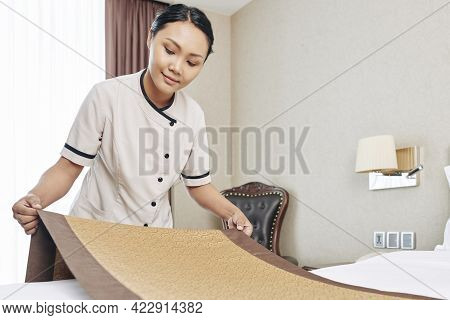 Pretty Smiling Hotel Maid Making Bed And Putting On Bed Runner As A Touch Of Elegant Flair