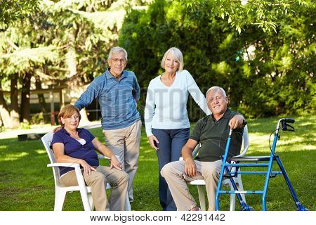 Many senior friends sitting together in a green garden