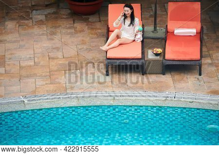 Happy Young Woman Sitting On Chaise-lounge By Swimming Pool, Drinking Sweet Cocktail And Talking On