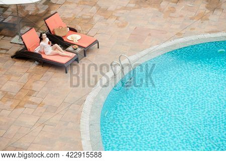 Beautiful Smiling Young Woman Relaxing On Chaise-lounge Of Spa Resort And Drinking Fruit Cocktail