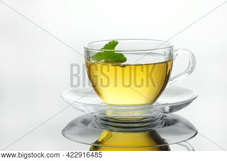 Yellow Herbal Tea In Glass Cup With Leaf. Close-up  Cup Of Freshly Brewed Hot Tea. Teacup On White B