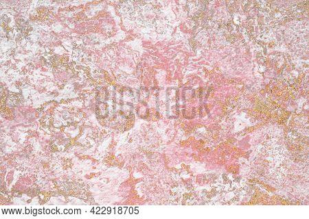 Grunge gold glitter on a pink textured background