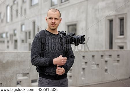 Portrait Of Professional Videographer Holding Dslr Camera On 3-axis Gimbal Over Grey Concrete Buildi