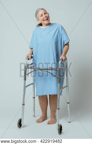 Happy patient in a hospital gown with a zimmer frame