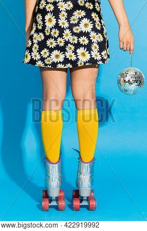 Feminine legs in a roller skates shoes and a disco ball