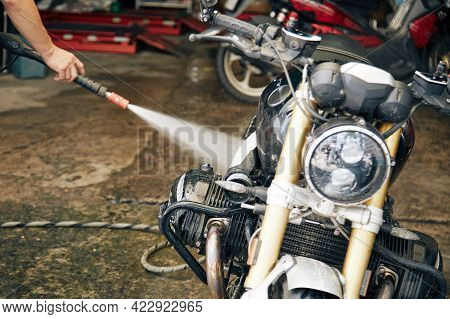 Man Rinsing His Motorcycle With Water In Garage After Riding On Muddy Road