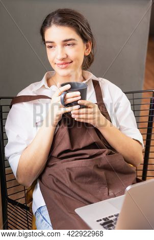 Vertical Angle Of Beautiful Caucasian Barista Woman Looks Blankly Outside Coffee Shop While Relaxing